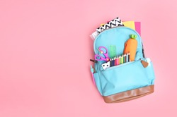 Backpack with school supplies top view on pink empty space background.