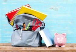 Backpack with school tools and piggy bank on turquoise background