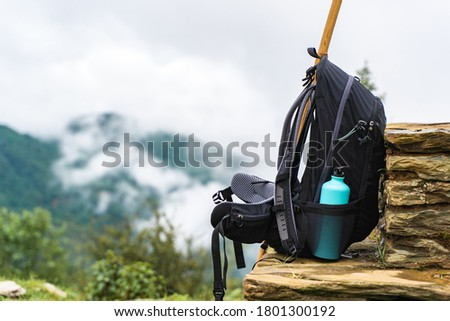 Backpack with water bottle and bamboo stick on stone fence near chasm. Mountains are hidden by clouds. Hiking and trekking concept. Imagine de stoc ©