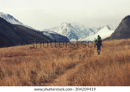 Backpacker go into the mountains. Happy travel concept. Mountain trekking. Man in harmony with nature. Autumn mountain landscape.