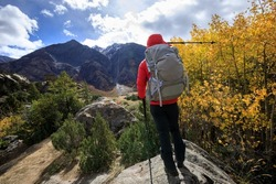 Backpacker hiking in high altitude winter mountains