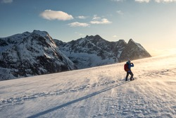 Backpacker man hiking and taking a photo on snow mountain with sunlight shine in the sunset at Lofoten Islands, Norway