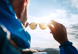 Backpacker man looking at bright sun through polarized sunglasses  enjoying mountain landscape. Eye & Vision Care human health concept image.