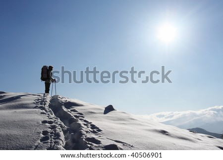 backpacker moving up in winter mountain under blue sky - stock photo