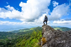 Backpacker or Traveler Man standing on mountains peak. Cheering successful  adventure travel lifestyle in vacations. Sport and active life summer outdoor happy emotions.Trekking Chiangmai. Thailand.