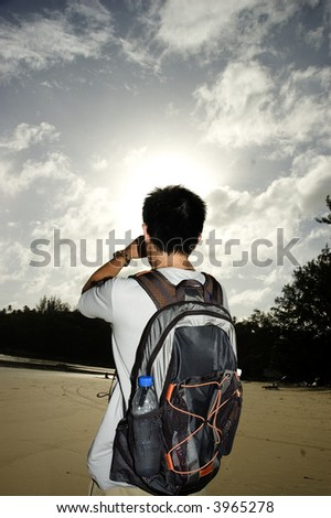 backpacker staring into sun on beach