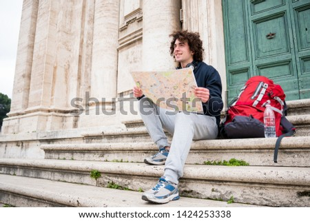 Backpacker tourist holding a tourist map #1424253338