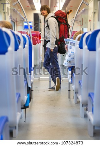 Backpacker with a skateboard on his back pack, leaning against a pole near the exit doors of a train compartment, seen through the aisle