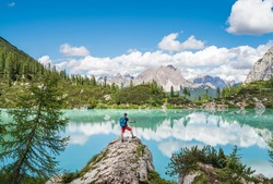 Backpacker with backpack enjoying the turquoise Lago di Sorapiss 1,925m altitude (mountain lake) view as he has mountain walk in Dolomite Mountains, Italy. Active people in nature concept.