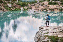 Backpacker woman with backpack and trekking poles enjoying the turquoise Lago di Sorapiss 1925m altitude lake view during mountain walking in Dolomite Mountains, Italy. Active people in nature concept