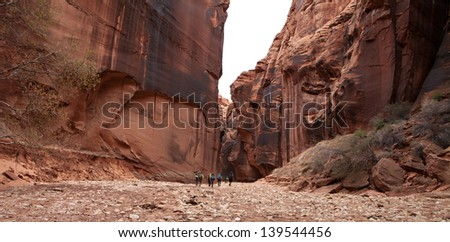 Backpackers make their way through the giant sandstone wall that tower above them in Buckskin Gulch, Utah