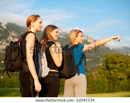Backpackers on travel - Group of three cute young girls with backpacks on a trip across grass field