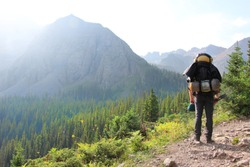 backpacking man in rocky mountains of colorado with sun shining