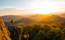 Backpacking on top of a mountain cliff. Hiker on the mountain trail with loose rocky ground and spectacular sunset view with mountain colorful autumn forests. Mountain meadow in spring or autumn.