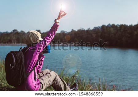 Backpacking woman hands holding a glass of warm coffee in the morning at outdoor,Lifestyle outdoor concept