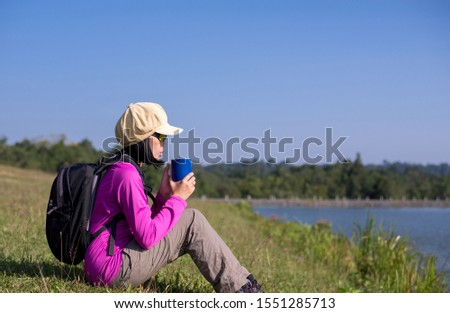 Backpacking woman hands holding a glass of warm coffee in the morning at outdoor,Lifestyle outdoor concept #1551285713