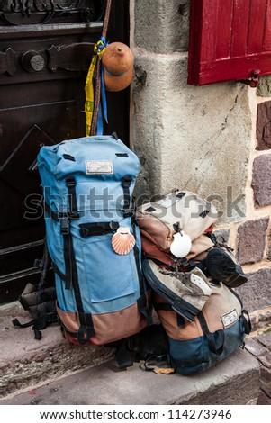 Backpacks on the facade of a hostel for pilgrims