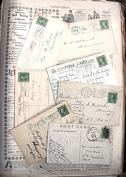 Backs of vintage postcards, early 1900s, on an 1872 newspaper for background. Postmarks and stamps.