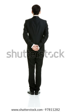 Backside of a businessman in a black suit, taken on white background.