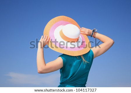 backside of a girl holding a big beautiful hat on the blue sky