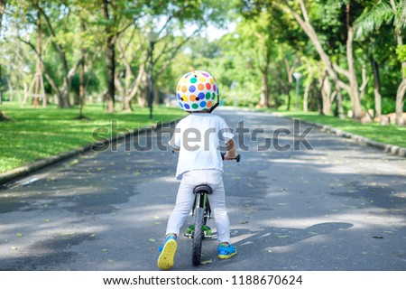Backside of cute Asian 2 years toddler boy child wearing safety helmet learning to ride first balance bike in sunny summer day, kid cycling at park, Explore & Appreciate Nature with toddlers concept