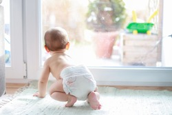 Backside of little baby boy in diaper crawling next to window home and looking outside during coronavirus,Covid-19 outbreak quarantine,social distancing concept.Focus on his leg.mixed Asian-German