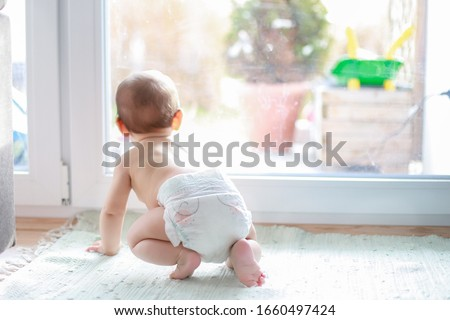 Photo of  Backside of little baby boy in diaper crawling next to window home and looking outside during coronavirus,Covid-19 outbreak quarantine,social distancing concept.Focus on his leg.mixed Asian-German
