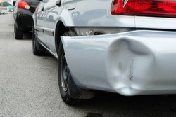 Backside of silver car get damaged by accident.