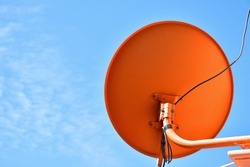 Backside of small parabolic antenna dish for television with blue sky background