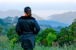 Backside shot of woman standing on  peak of the hill and enjoying beautifull landscape at San Pakiea viewpoint, Chiengmai, Thailand.