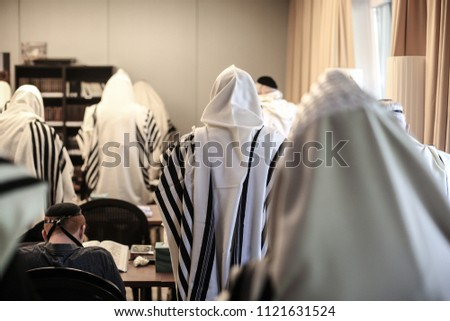 Backside view of congregants in a Jewish synagogue wrapped in prayer shawls during prayer Photo stock ©