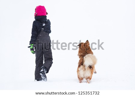 backside view of girl and dog walking in the snow