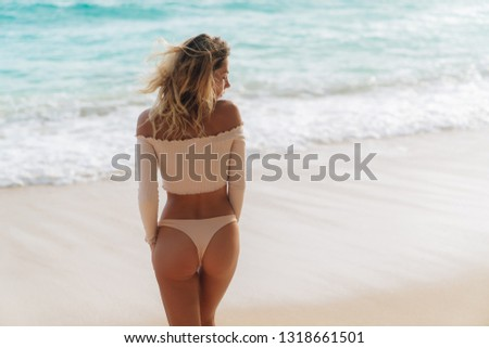 Backside view of girl with sexy booty in pink bikini resting on deserted beach. Beautiful model in swimwear walks along white sand on tropical island
