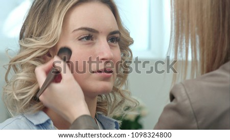 Backstage in the film. Make-up artist doing professional make-up for actress
