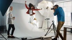 Backstage of the Photo Shoot: Moment Photographer Taking Photos of Jumping Beautiful Black Model with Professional Camera. Fashion Magazine Studio Photoshoot