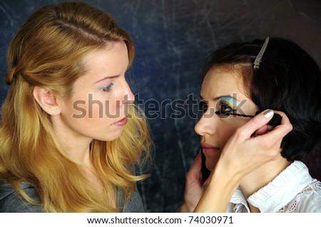 Backstage scene: esthetician doing model makeup.