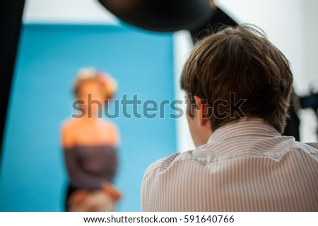 Backstage shot of a professional photoshoot in a studio with a model, photographer and light equipment.
