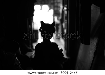 Backstage theater; silhouette of a child actor in cat ears handband