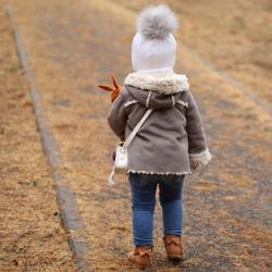 Backview of little girl in lightbrown short sheepskin coat, holding doll in park on cold day.