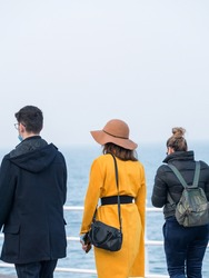 Backview with two girls and a man walking on the Constanta seafront (Faleza Cazino Constanta) in Romania.