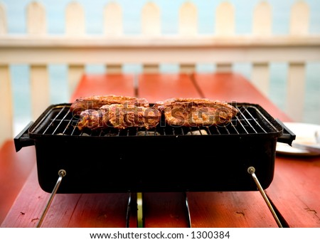 Backyard BBQ on picnic table with white picket fence for background