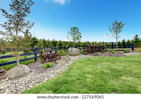 Backyard beautiful spring landscape with fence, rocks and green grass.