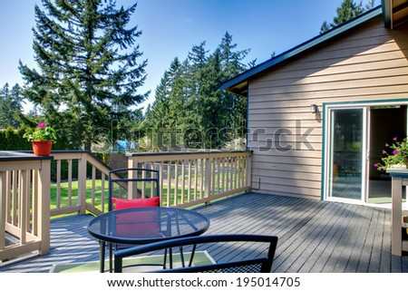 Backyard deck with table set decorated with flower pots #195014705