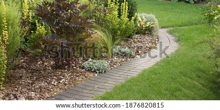 Backyard Garden Modern Design Landscaping. Decorative Garden Winding Pathway Walkway From Black Bricks. Back Yard Lawn And Natural Mulched Border Between Grass And Curved Brick Paving. Path To House. Foto stock ©