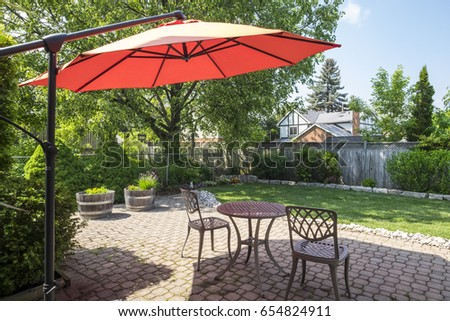 Backyard Garden with Bright Orange Cantilever Umbrella and Bistro Set #654824911