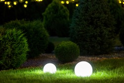 backyard ground 2 light garden with lantern electric lamp with sphere diffuser in green grass with thuja bushes and stone mulching in park with landscaping, closeup night scene nobody.
