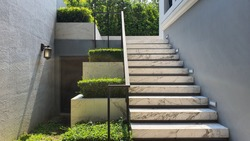 Backyard in the afternoon mood. White marble stairs and plant pots. Green natural in backyard. Bangkok, Thailand.
