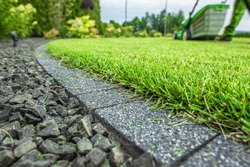 Backyard Lawn Grass Field Cobble Edge. Grass Mowing and Edges Finishing. Gardening and Landscaping Industry Theme.