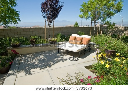 Backyard oasis and suburban retreat with flowers, lounge chair, and patio