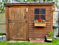Backyard outdoor garden tool shed with decorative elements to blend into landscaped yard and garden